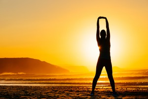Fitness woman exercising and stretching arms on beautiful summer sunset or morning at beach. Female doing relaxing yoga and breathing exercises.